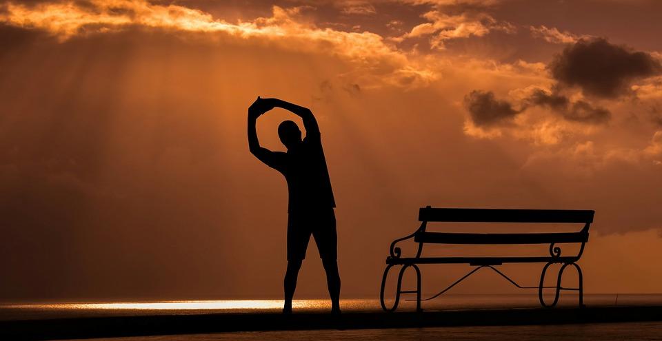 hombre estirando calentamiento deportivo atardecer